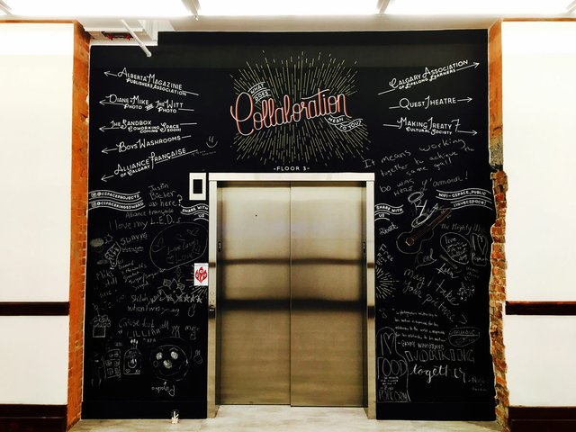 A chalkboard frames the elevator in the repurposed school