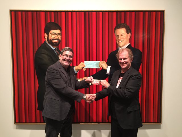 "Peter Boyd and Chris Cran re-enact ""The Cheque"" depicting an early purchase prompted by Boyd's desire for a Cran painting when none was available and his willingness to go along with Cran's project. 2016 (photo by Jordan Boyd)"