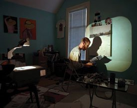 """An artist painting with the aid of an overhead projector"""