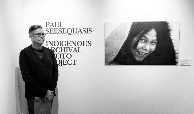 "Paul Seesequasis stands with Rosemary Gilliat Eaton's ""Portrait of Inuit artist Napachie Pootoogook, Cape Dorset, Nunavut"