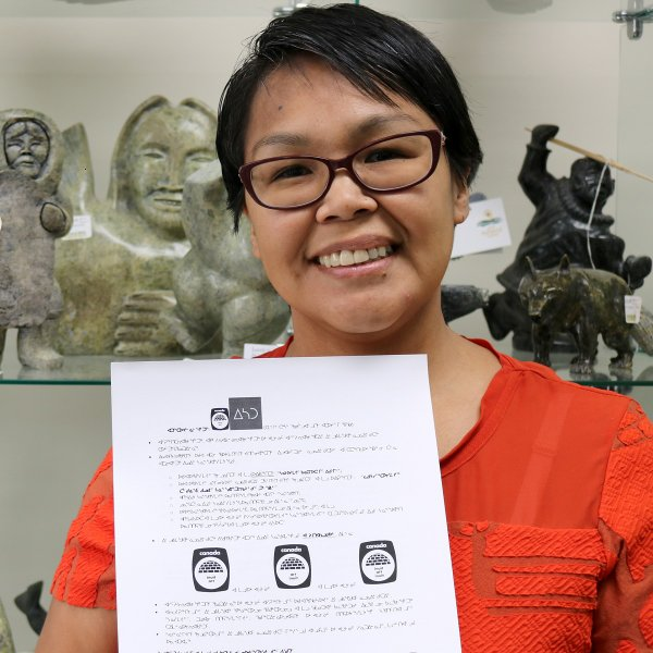 Lori Idlout, owner of Carvings Nunavut, with a signed copy of the first new Igloo Tag license agreement in over 45 years. (photo courtesy Inuit Art Foundation)