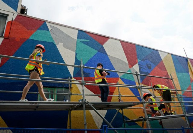 In a back alley near 3rd Street & Lonsdale Avenue, a group of youth have been transforming an old wall into a painted mural full of colour and history