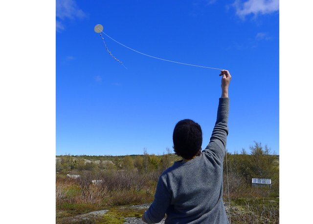 Flying a boulder kite at a 2018 workshop hosted by the Museum of the Flat Earth on Fogo Island, Nfld.