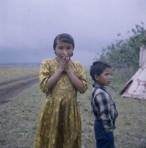 "Rosemary Gilliat, ""Young girl and boy standing on grass, between a teepee and a dirt road, Ghost River, Alberta,"" ca. 1962"