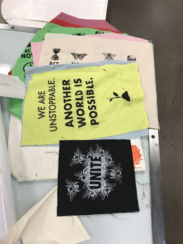 Protest signs printed at the Society of Northern Alberta Print-Artists in collaboration with climate action groups, using designs by artists around the world.