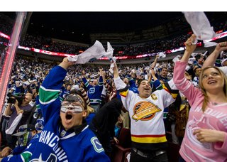 Vancouver Canucks fans go crazy after their team scores against the Calgary Flames during the second period of Game 1