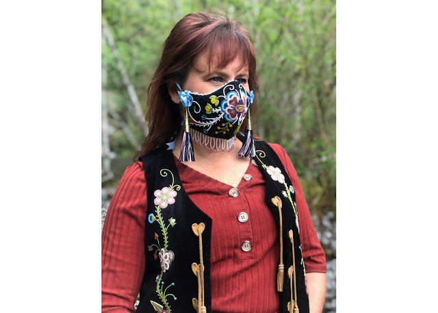 "Lisa Shepherd wears her mask ""Wâhkôhtowin,"" a Cree word that embodies relationship not just to family but to everything, including plants, animals, the earth and the sky. (photo by Martin Shepherd)"