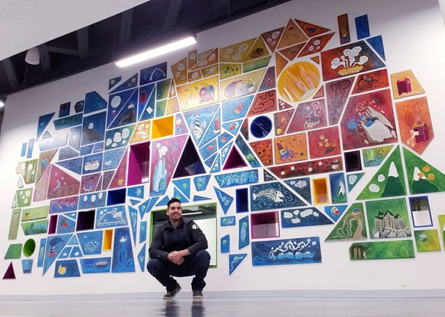 Ricardo Copado poses with his mural at Edmonton's downtown public library. (courtesy the artist)
