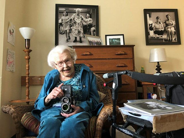 Thelma Pepper poseswith a Rolleiflex camera in 2018 at a seniors' home in Saskatoon. (photo by David Gutnick)