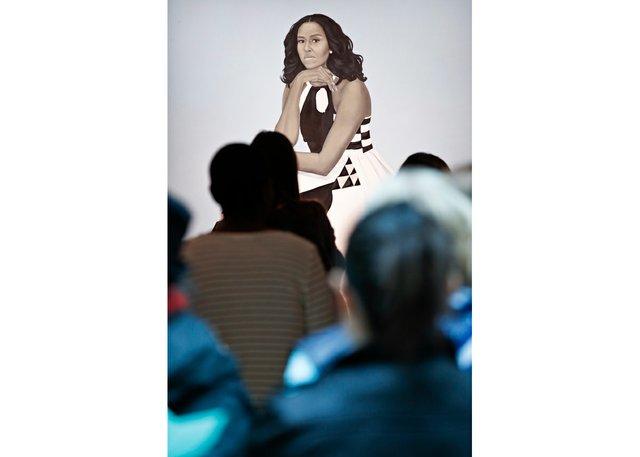 Visitors encounter AmySherald'sportrait of Michelle Obama at the National Portrait Gallery. (photo by PaulMorigi)