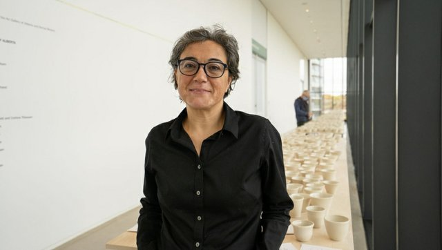 """Nurgul Rodriquez with her work """"Out of Place,"""" Remai Modern, December 2020"""