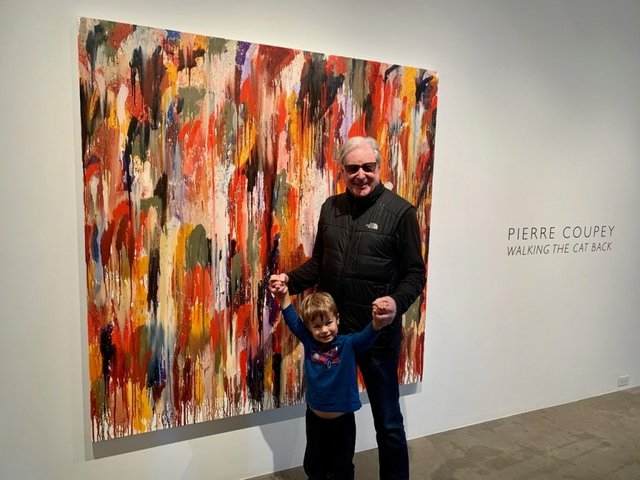 """Pierre Coupey and his grandson stand next to his 2020 oil painting """"Algonquin II""""  at Gallery Jones in Vancouver. (photo by Kristin Man)"""