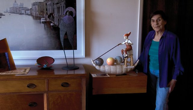"Joan McConnell with a stoneware sculpture by Byungjoo Suh called ""Heron of Alexandria."""