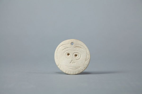 """Carved bone depicting a happy face"""