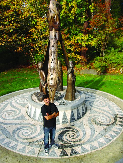 """Ts'uts'umutl Luke Marston poses with his sculpture, """"Shore to Shore"""""""