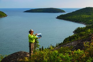 "Joanie McGuffin holds a copy of a Lawren Harris painting, ""Island Lake Superior"""