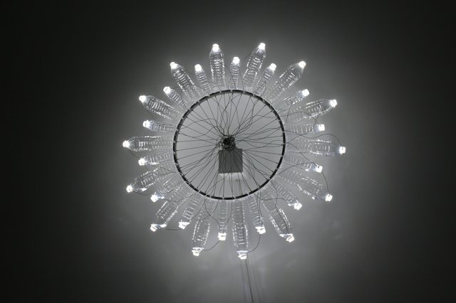 """DIANE LANDRY """"Solo Knight II"""", 2014 mural automation bicycle wheel, plastic water bottles, mineral oil, LED, aluminum, motor, gear, ball bearing 135 cm diameter"""