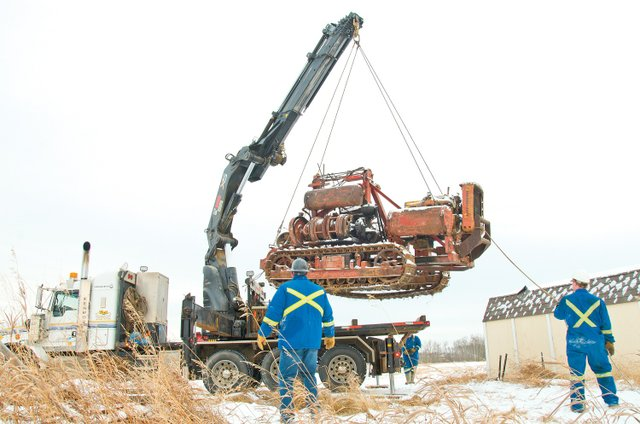 Workers load a trencher in Fort St. John, last February